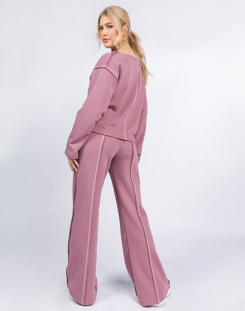 the model looks over her shoulder to show the back of the Naz Contrast Stitch Logo Jumper in Blush worn with the matching trousers