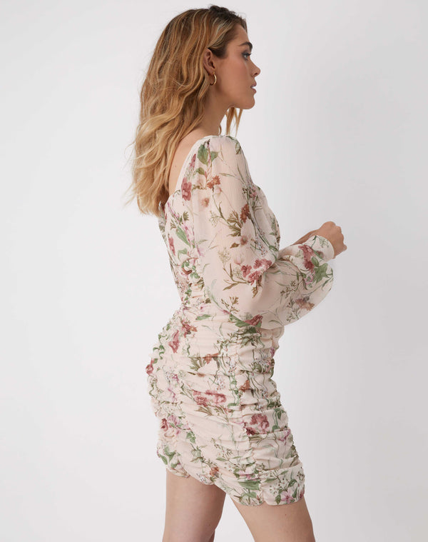 model faces sideways in the jana gathered floral mini dress with long sleeves and her hands in front of her