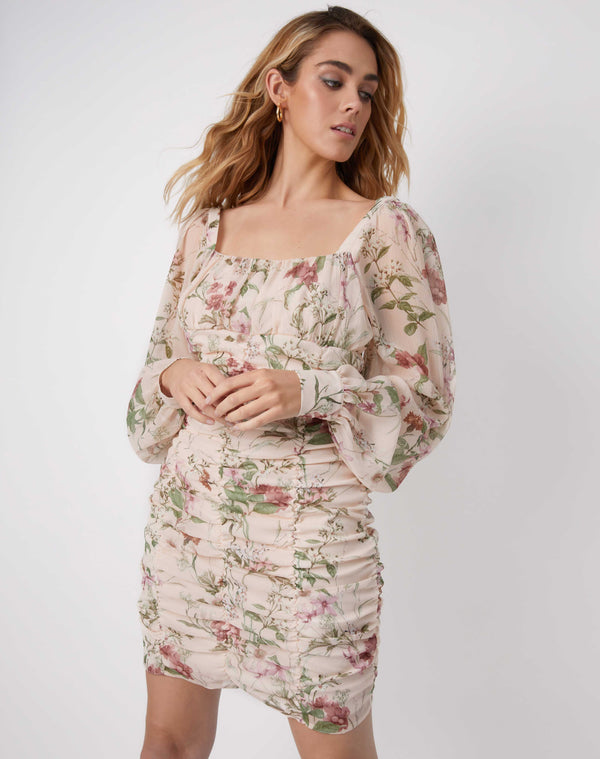 model wears the jana gathered floral mini dress in a pale beige with long sheer sleeves and square neck