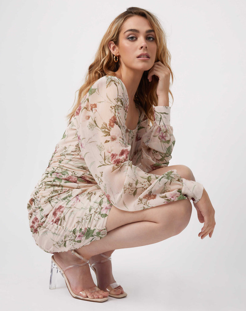 model crouches and leans her arms on her knees in the jana gathered floral mini dress in pale pink with nude perspex heels