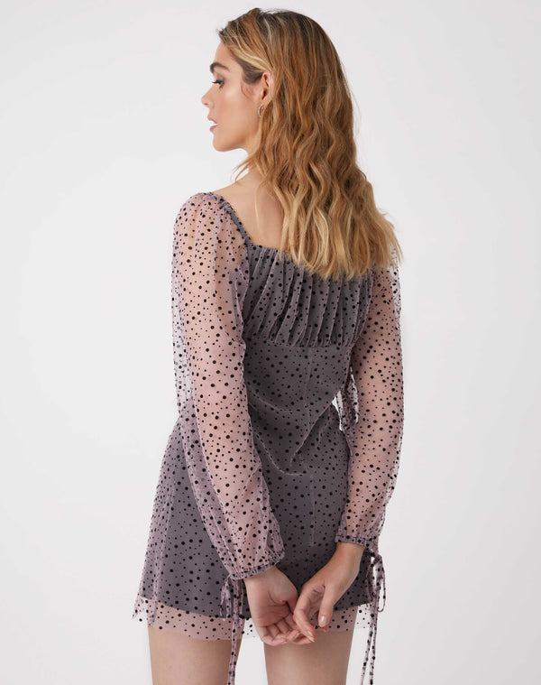 we see the back of the celeste pink mesh dress with black flocked polka dots and sheer sleeves on the model facing away from the camera with her arms behind her