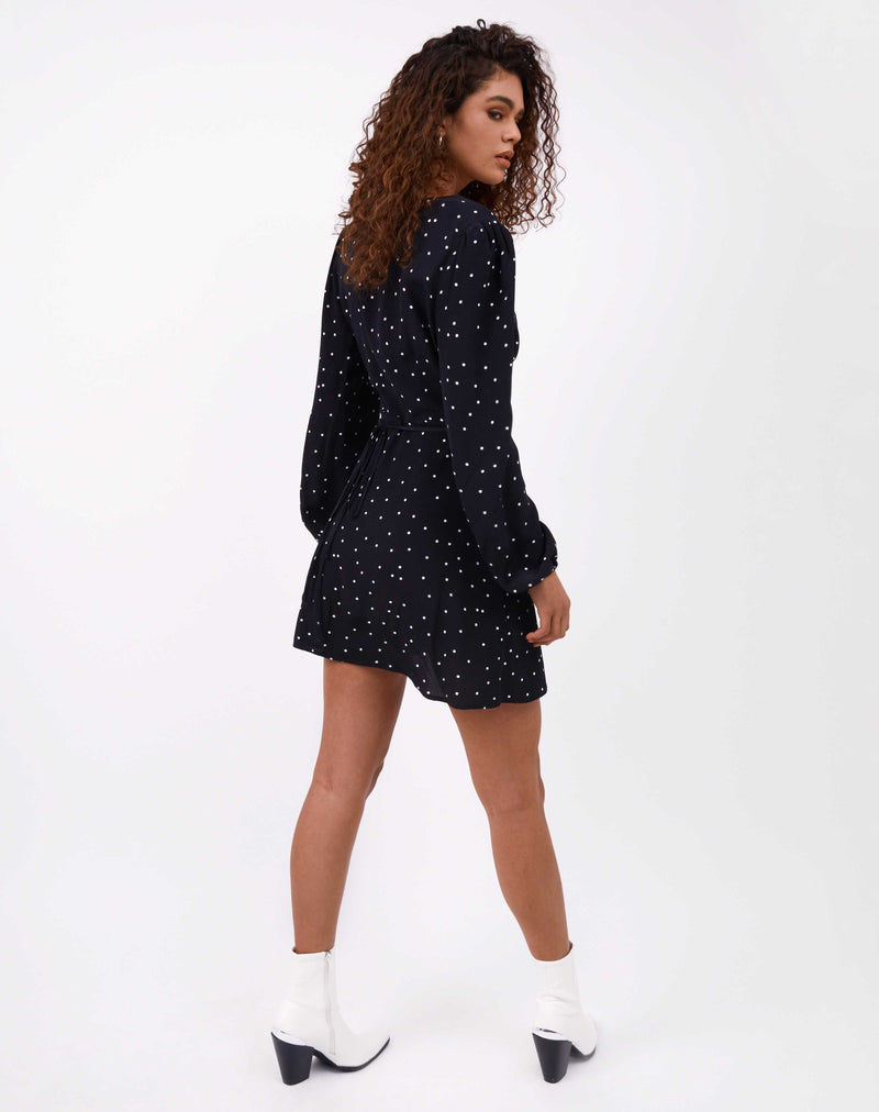 back image of model wearing polka dot adina wrap dress in white boots against white background