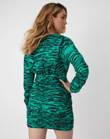 a model looks over her shoulder while we see the back of the esme green animal print dress with one hand on her him