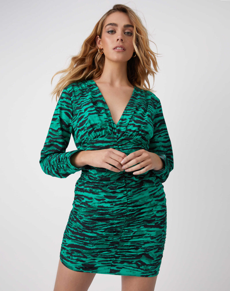 a model wear the esme green animal print gathered dress with long sleeves and both hands in front of her