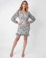 the model holds her hands on her hips wearing the Ruby Ruched Wrap Dress In Animal Print