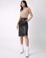 model has hands in the pocket of the Vita Black PU Midi Skirt With Pockets with a ribbed top and white boots