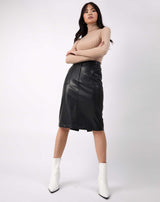 model has arms crossed wearing the Vita Black PU Midi Skirt With Pockets with a ribbed jumper and white boots