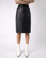 a cropped image of the Vita Black PU Midi Skirt With Pockets on a model with white boots