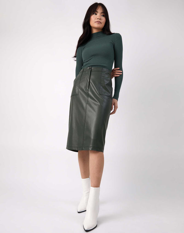 model wears Vita Green PU Midi Skirt With Pockets with ribbed green knit and white boots