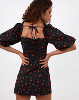 model has hands on her hips while facing away from the camera showing the tie back of the charlotte rose print puff sleeve dress in black