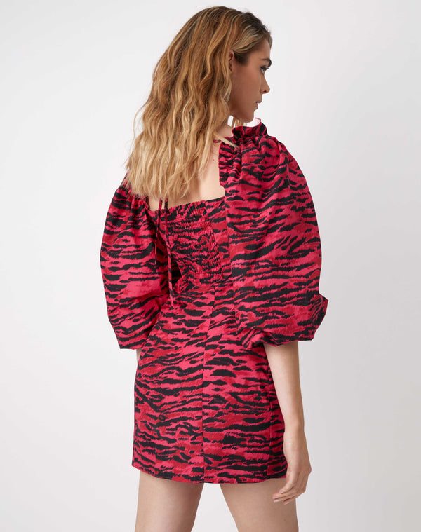 we see the model from behind wearing the charlotte pink animal puff sleeve dress with square neckline and mini length