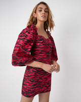 the model looks at the camera with hands in front of her wearing the charlotte pink animal zebra print puff sleeve dress