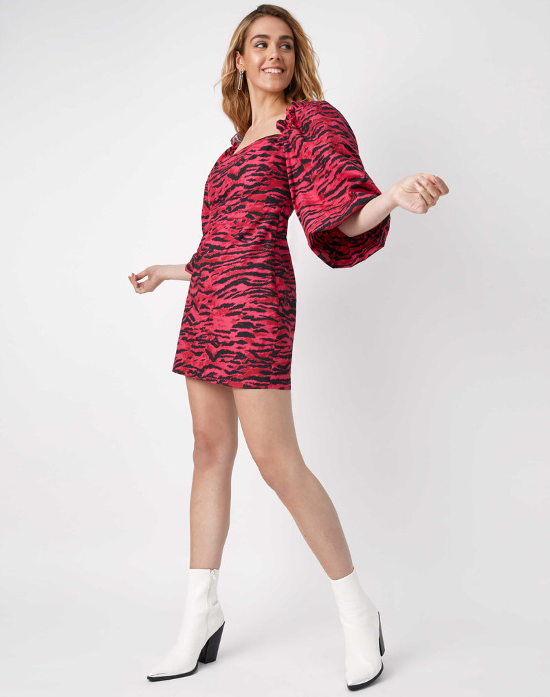 the model smiles and moves while wearing the charlotte pink animal puff sleeve dress with white cowboy style boots