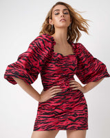 model has both hands on hips and hair blowing while wearing the charlotte pink animal zebra print puff sleeve dress