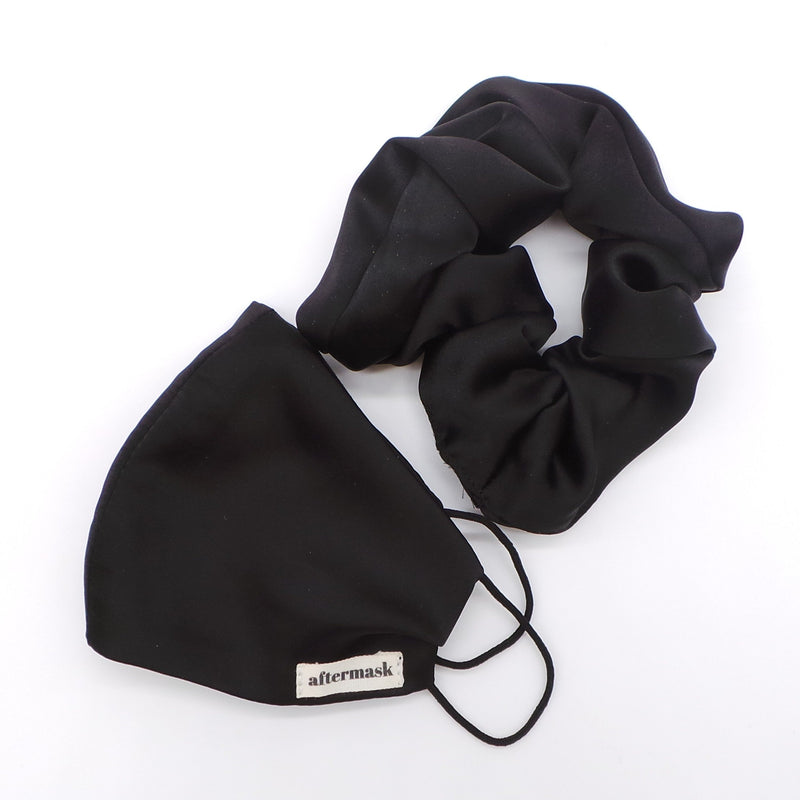 a close up image of a black hair scrunchie on a white background alongside a black aftermask mask