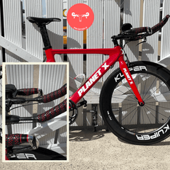 Red PlanetX Timetrial bike wrapped in black bar tape with red droplets