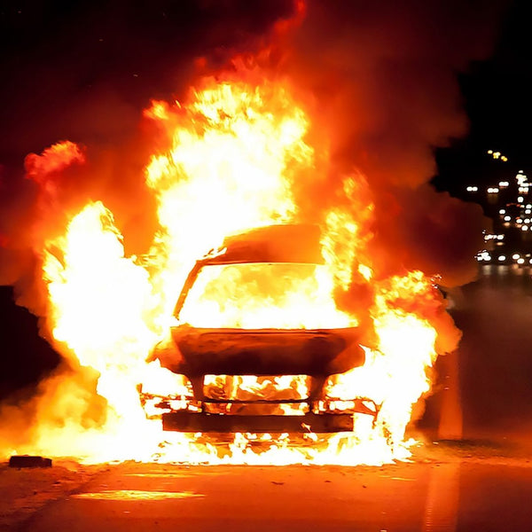 A car on fire in the middle of the road.