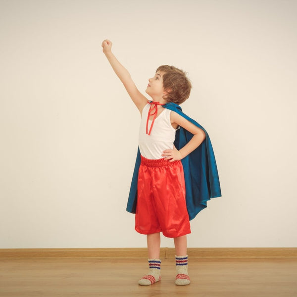 Boy Wearing A Blue Cape and Red Shorts Posing as a Superhero