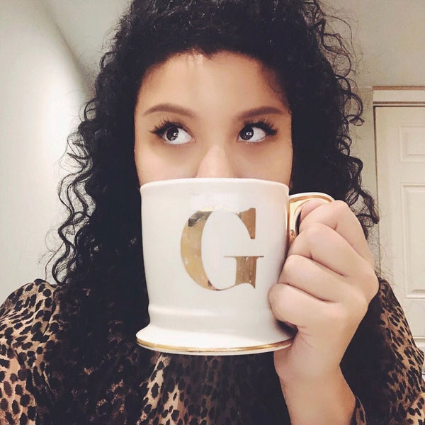 "Gabriela Ariza holding a coffee mug with the letter ""G"" printed on it."