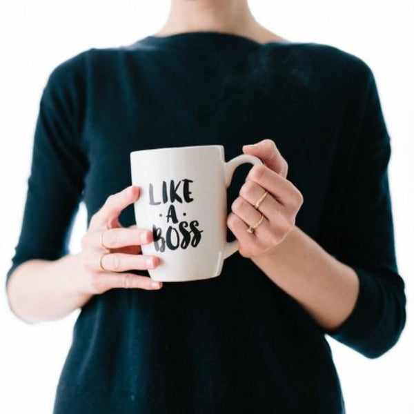 "Woman Holding a Coffee Mug That Says ""Like a Boss"""