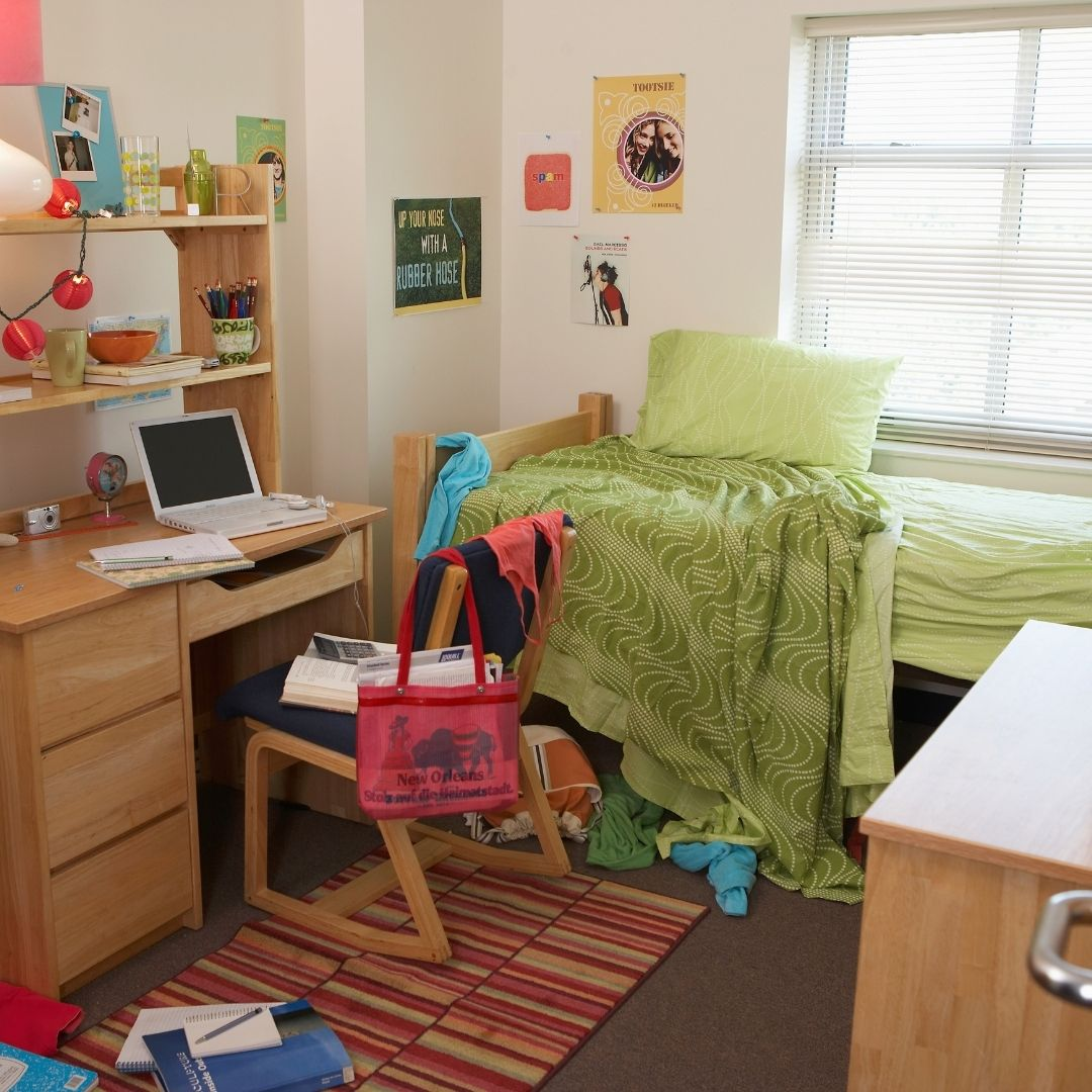 A messy college dorm room with a bed and computer desk in frame.