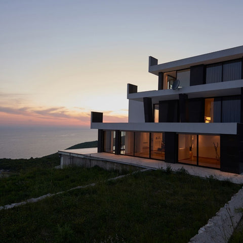 An amazing house along the shore at sunset.