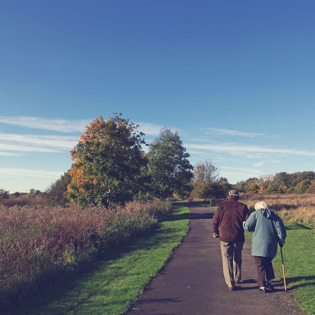 Two people walking on a park trail during retirement.