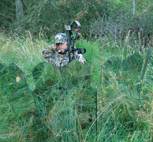 camouflaged hunter takes aim behind blind