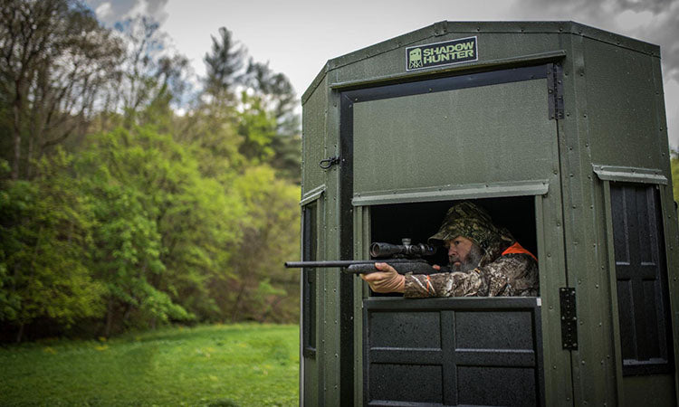 a hunter aiming from a blind window