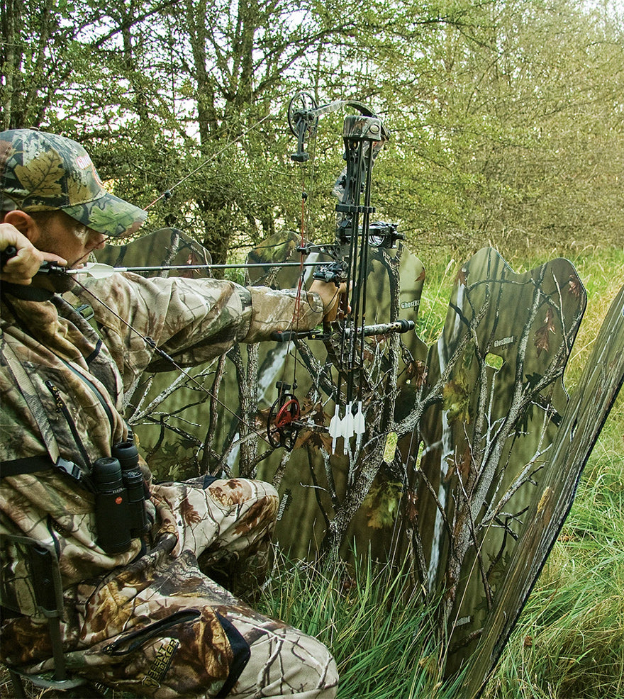a hunter using a compound bow behind a blind