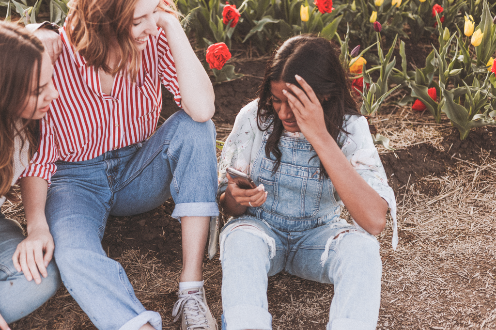 A photo of three girls sitting outside in jean overalls, schmoozing, while one looks at her phone. There are red and yellow roses behind them.