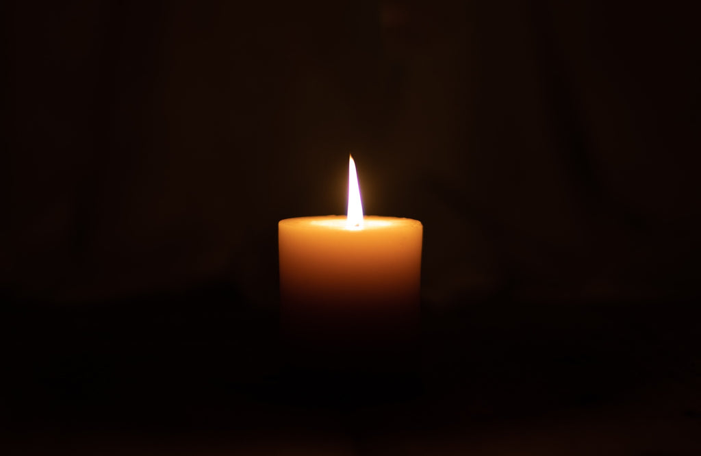 A photo of a lone yellow candle burning amidst blackness all around.