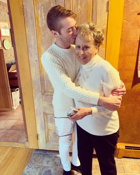 A photo of bubuleh founder Jordan Star in a white sweater and jeans, hugging his grandmother, also in white.