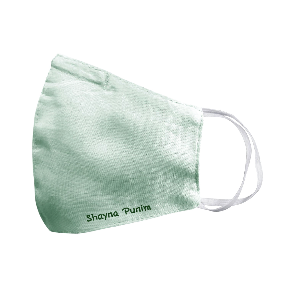 "A mint green spring linen face mask that says ""shayna punim"" embroidered on the bottom, with white ear loop straps."