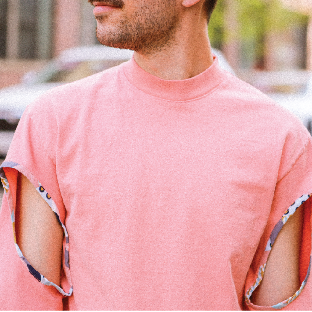 A man wearing the holey salmon top showcasing a retro pattern on the sleeve cutouts, shot in Williamsburg, Brooklyn in the background.
