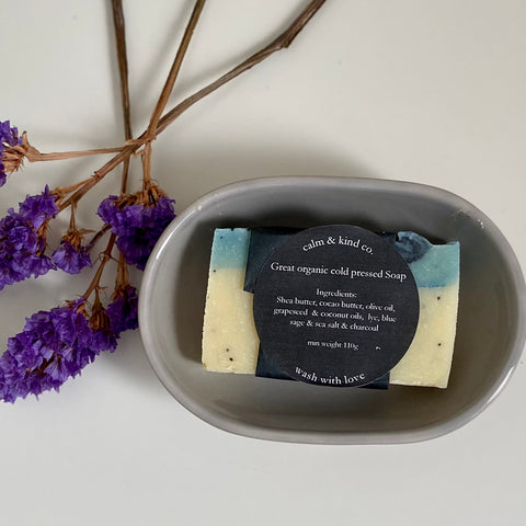 Dried purple flowers on left had side. Grey soap dish with cream and blue coloured soap in it. Soap has black label that states calm & kind co. Great organic cold pressed soap. Ingredients: Shea butter, cocoa butter, olive oil, grapeseed & cocnut oils, lye, blue sage & sea salt & charcoal