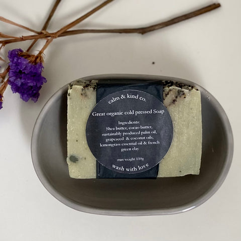 Dried purple flowers in top left hand corner. Grey soap dish with a grey soap in it. Soap has a black label that states calm & kind co. great organic cold pressed soap. ingredients: shea butter, cocoa butter, sustainably produced palm oil, grapeseed & coconut oils, lemongrass essential oil & french green clay. wash with love
