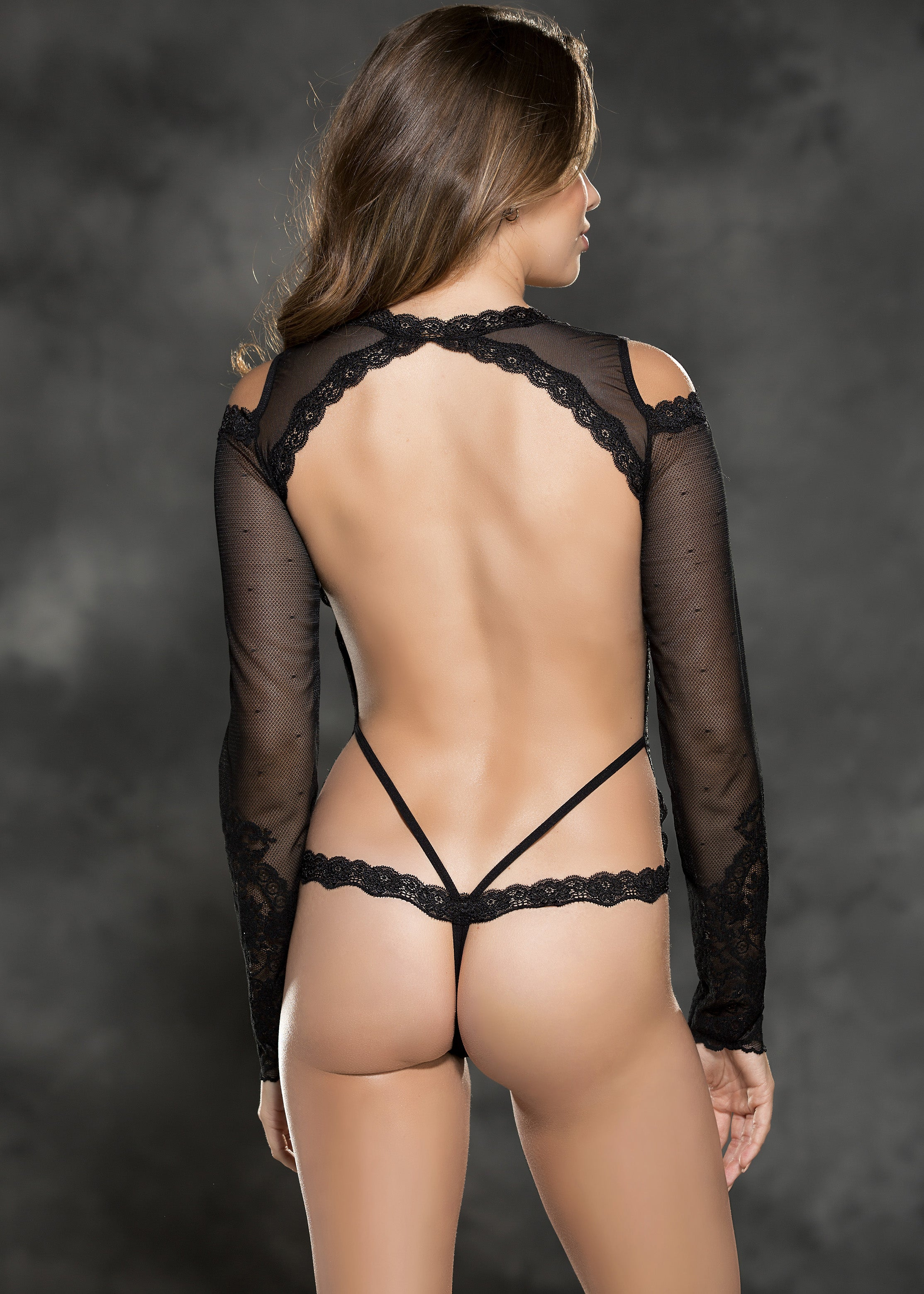 Strategically designed lace bodysuit with long sleeves, attractive cut out shoulders and an open thong back.
