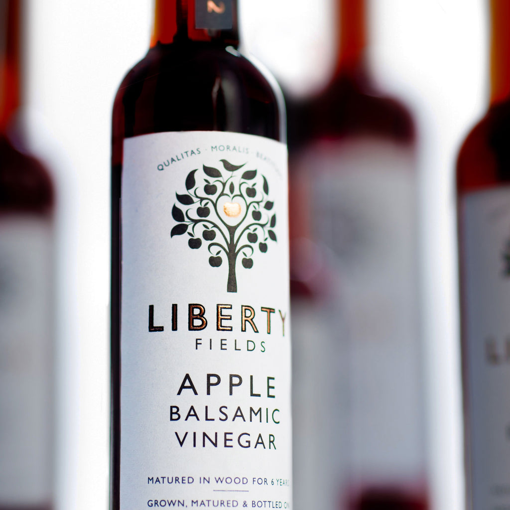 A bottle of Balsamic Vinegar in sharp focus, a brown bottle with a white label showing the black logo of Liberty Fields depicting an apple tree. Other bottles of Balsamic vinegar are out of focus behind the main bottle.