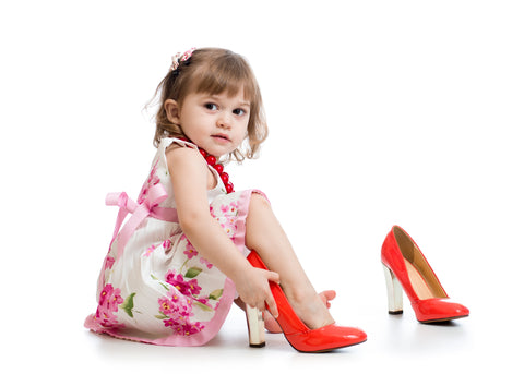 Baby girl wearing oversized high heels. Size guide