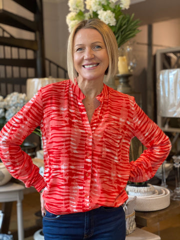 Emma in the Eden shirt in a red and white tie dye print.