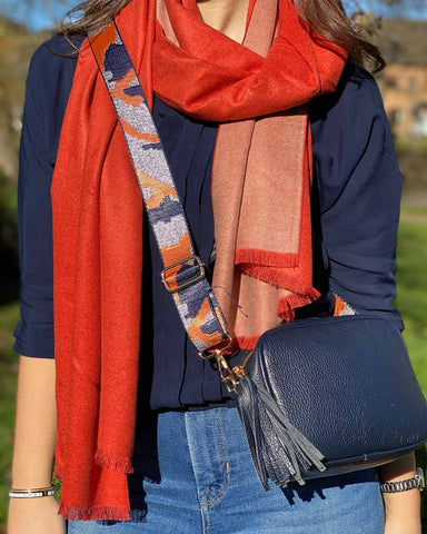 Photo of woman in white gingers fashion accessories including scarf, bag strap and leather tassel bag.