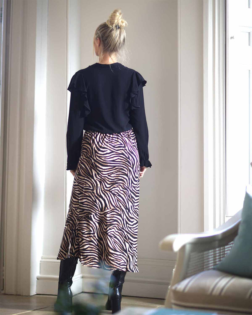 Behind shot of woman inside posing in black blouse and zebra printed skirt inside a house.