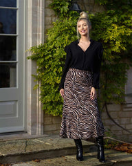 Woman in black frilled blouse and zebra printed black and brownskirt. Model is outside.