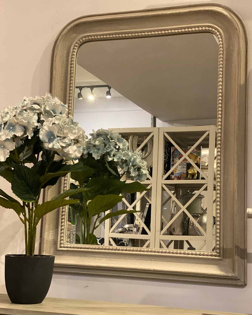 Large grey mirror with beaded detailing around the edge.