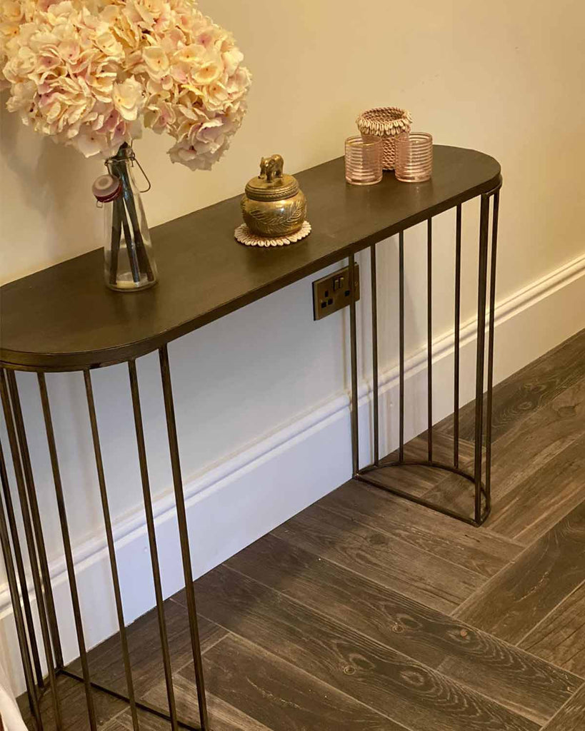Metal black console table with two ends consisting on many legs.