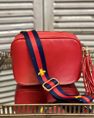 Red tassel bag with navy/red stripe print with bee detail going across it. On a mirrored table.