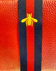 Close up image of red/navy stripe with bee detail bag strap.