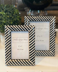 Two black and white striped photo frames one small one large, with white inserts. Pictured on white table.