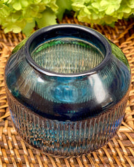 Blue glass teal light holders, with ridged detailing pictured on rattan placemat.